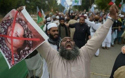 un-partisan-du-parti-musulman-extremiste-aswj-ahle-sunnat-wal-jamaat-proteste-contre-l-acquittement-de-la-chretienne-asia-bibi-dont-il-brandit-le-portrait-barre-de-rouge-a-islamabad-le-2-novembre-2018.jpg